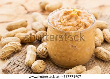 Creamy peanut butter on old wood table. - stock photo