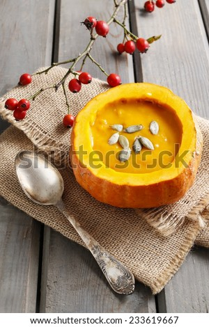 Creamy pumpkin soup on rustic wooden table - stock photo
