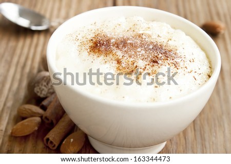creamy rice pudding with cinnamon powder,cinnamon sticks and almonds - stock photo