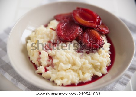 Creamy rice pudding with plums - stock photo