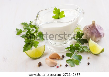 creamy sauce on glass sauce boat and ingredients - stock photo