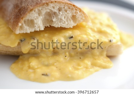 Creamy scrambled eggs with bread in French style. - stock photo