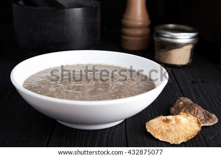 Creamy vegan mushroom soup with champignon and shiitake in white bowl. Dark photo with black wood background. Mortar, pepper mill and jar with mushroom powder on back. Dry shiitake on front. - stock photo
