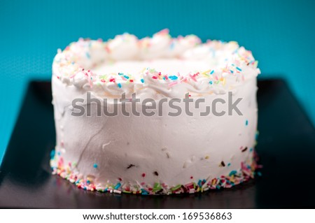 Creamy white chocolate and sweet birthday cake isolated on black plate and turquoise background - stock photo