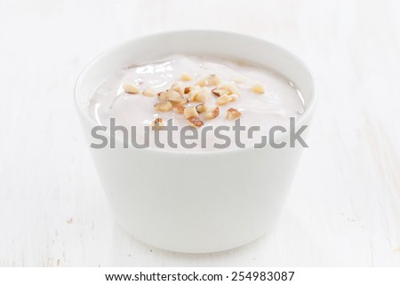 creamy yogurt with nuts in a white bowl, close-up - stock photo
