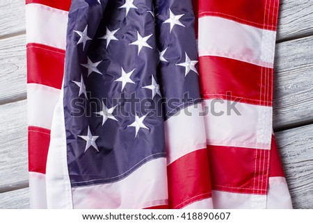 Creased national flag of US. Flag on white wooden background. Banner of three colors. Faith, hope and patriotism. - stock photo