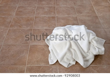 Creased white towels on ceramic floor in a laundry room or bathroom. - stock photo