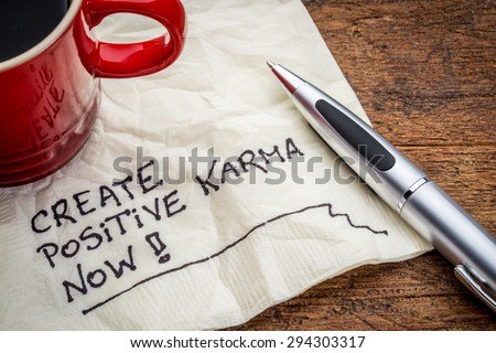 create positive karma now - motivational handwriting on a napkin with cup of coffee - stock photo