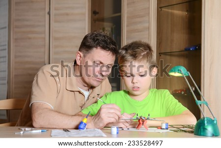 Creating the model plane. Happy son and his father are making aircraft model. Hobby and family  concept. - stock photo