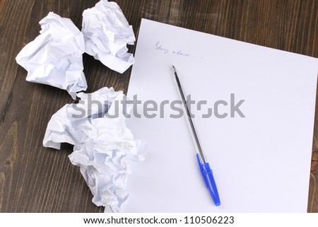 Creation of composition and crumpled sheets on wooden table - stock photo
