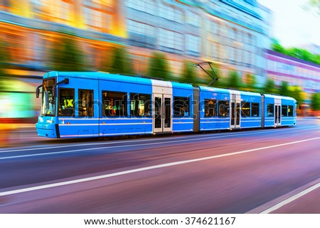 Creative abstract city transportation and business travel technology industrial concept: blue modern tram on urban city street with motion blur effect in Stockholm, Sweden - stock photo