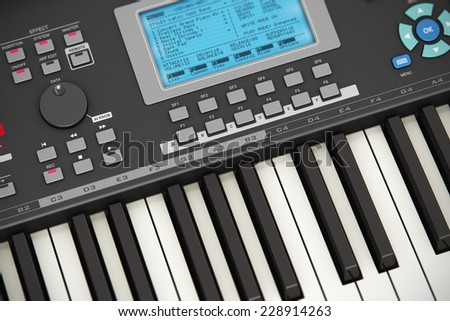 Creative abstract electronic music instrument and art creation concept: macro view of black professional digital musical piano synthesizer with LCD display screen, buttons and other controls - stock photo