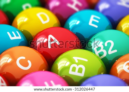 Creative abstract health lifestyle, diet and healthy eating and nutrition food concept: macro view of color balls, pills or tablets with vitamins names with selective focus effect - stock photo
