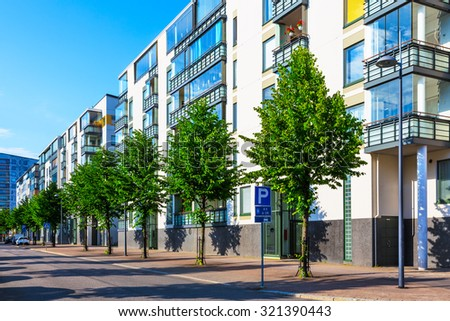 Creative abstract house building and city construction industry concept: summer outdoor urban view of urban city street with modern real estate homes - stock photo