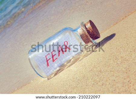 "Creative anxiety and fear concept.  Bottle with a message ""Fear"" lying on beach - stock photo"