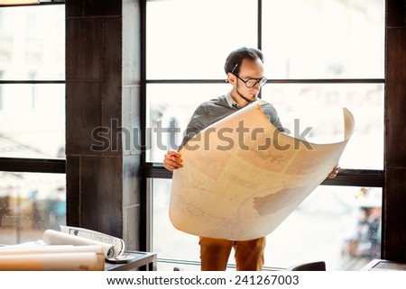 Creative architect looking on the big architectural drawings in front of the big window - stock photo