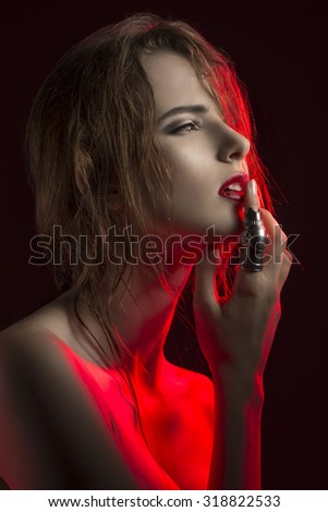 creative beauty fashion portrait of charming female with erotic expression in red half-light with wet hair, luxurious lips and artistic ring  - stock photo