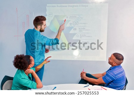 Creative brainstorming. Rear view of group of cheerful business people in smart casual wear discussing infographics and writing on the board in the meeting room - stock photo