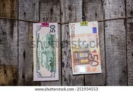 Creative business finance making money concept. Money on a clothespin on a wooden background. US dollars, euros - stock photo