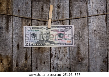 Creative business finance making money concept. Money on a clothespin on a wooden background. US dollar new - stock photo