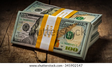 Creative business finance making money concept - panorama of stacks of new 100 US dollars 2013 edition banknotes (bills) bundles isolated on wooden background - stock photo