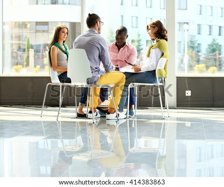 Creative business people meeting in circle of chairs - stock photo