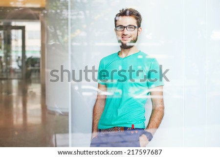 creative business person in a blank t-shirt, view through the window - stock photo