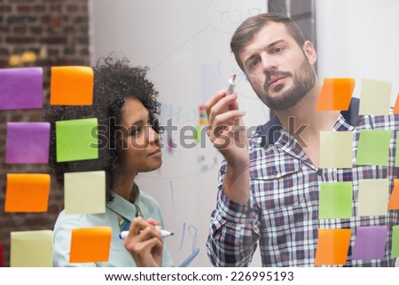 Creative business team looking at sticky notes on window - stock photo
