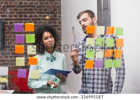 Creative business team using digital tablet by sticky notes on window - stock photo