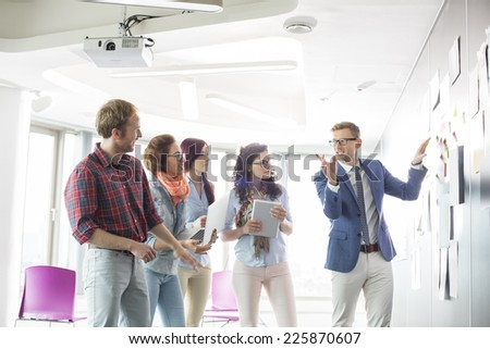 Creative businessman giving presentation to colleagues in office - stock photo