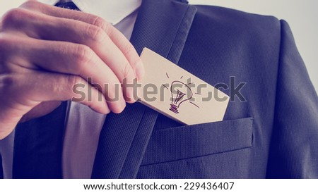 Creative businessman with a great idea withdrawing a card with a hand-drawn light bulb from his suit pocket, close up of his hand with retro filter effect. - stock photo