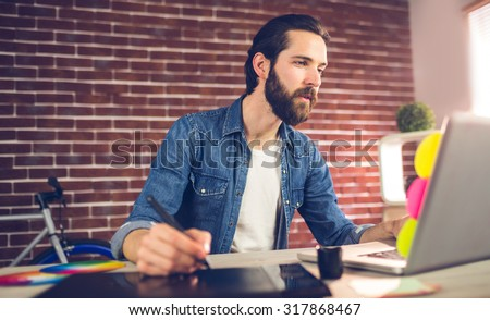 Creative businessman writing on graphic tablet while using laptop in office - stock photo