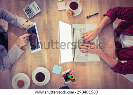 Creative businessmen working on electronic devices in the office - stock photo