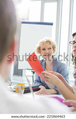 Creative businesswoman in meeting with colleagues at office - stock photo