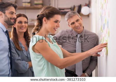 Creative businesswoman pointing sticky notes on wall with colleagues. Group of business people working on new project with many sticky notes. Young creative teamwork working at office.  - stock photo