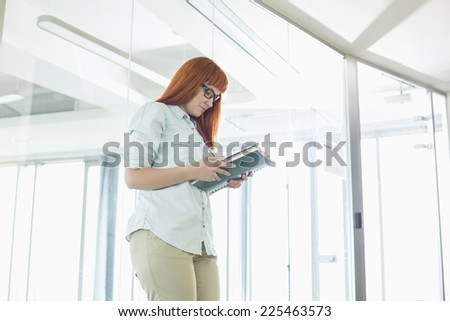 Creative businesswoman reading file in office - stock photo