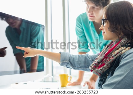 Creative businesswoman showing something to colleague on desktop computer in office - stock photo
