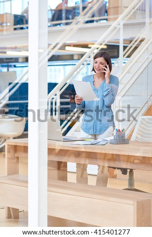 Creative businesswoman talking on phone while holding paperwork  - stock photo