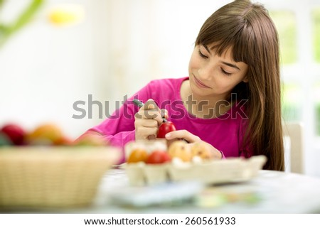 Creative cute girl painting Easter eggs - stock photo