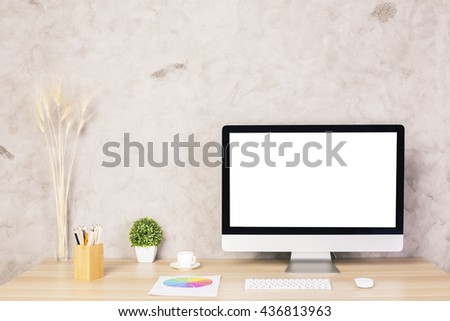 Creative designer desktop with blank white computer monitor, keyboard, coffee cup, plant, other decorative items and colorful diagram. Mock up - stock photo