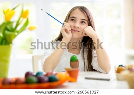 Creative girl with Easter eggs, thinking  - stock photo