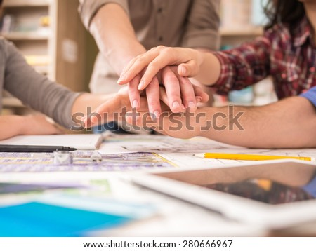 Creative group of designers putting hands together. Team work. - stock photo