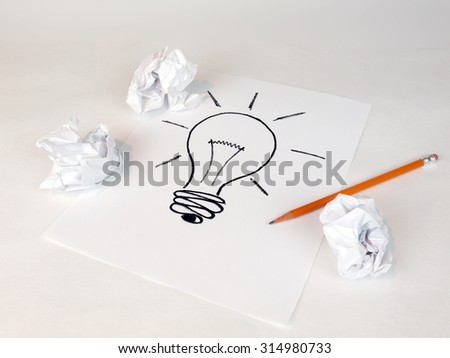 creative idea concept for business and intellectual layouts featuring an idea lightbulb with crumbled paper and pencils - stock photo
