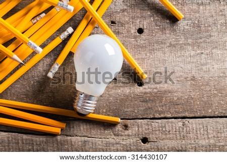 Creative ideas, light bulb and pencils on the table - stock photo
