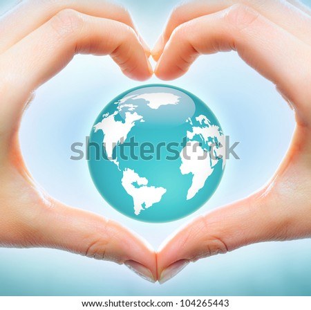 Creative image of earth model inside heart made up of human hands - stock photo