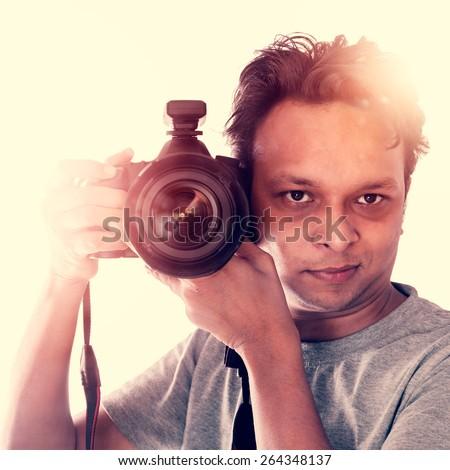 Creative Indian Photographer taking photo with camera - stock photo