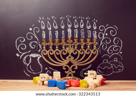 "Creative Jewish holiday Hanukkah background with menorah and spinning tops over chalkboard with hand drawing. The Hebrew letters are the first letters of the words ""A great miracle happened here."" - stock photo"