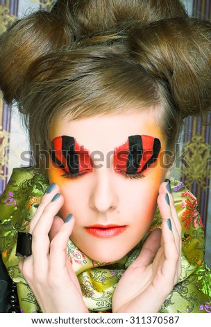 Creative lady.Young woman in dramatic image and with red and black artistic visage. - stock photo