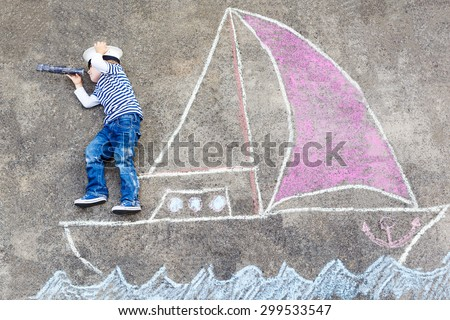 Creative leisure for children: Funny little boy of four years having fun with ship or boat picture drawing with chalk. - stock photo