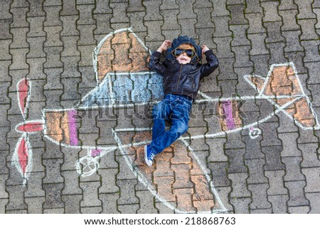 Creative leisure for children: Funny little child of four years having fun with airplane picture drawing with chalk. - stock photo